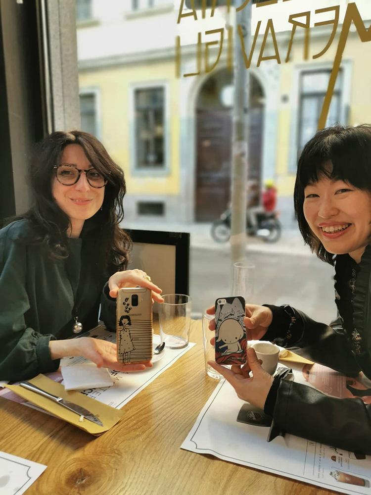Silvia Trappa et Maiko Kobayashi montrant le dos de leur smartphone avec les couvertures de leurs livres dans la collection aKa